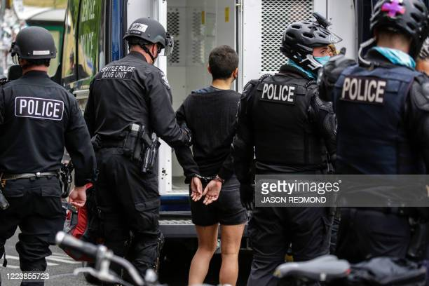 Seattle Police arrest a woman after demonstrators blocked the intersection of East Pine Street and 11th Avenue following the clearing of the Capitol...