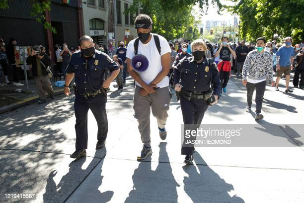 TOPSHOT Seattle Police Assistant Chief Adrian Diaz and Assistant Chief Deanna Nollette walk with a protester who wished to remain anonymous as he...