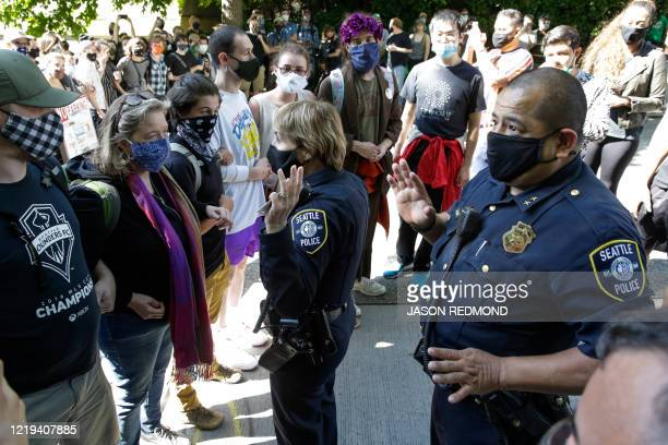 TOPSHOT Seattle Police Assistant Chief Deanna Nollette and Assistant Chief Adrian Diaz are blocked by protesters from entering the newly created...
