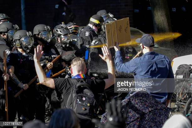"""Seattle police officers deploy pepper spray as they clash with protesters following the """"Youth Day of Action and Solidarity with Portland""""..."""