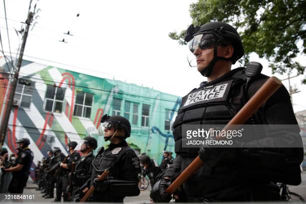 Seattle Police stand guard outside a precinct as people protest the death of George Floyd in the Capitol Hill neighborhood of Seattle Washington on...