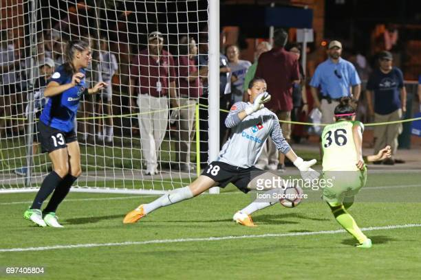 Seattle Reign FC forward Nahomi Kawasumi beats FC Kansas City defender Brittany Taylor and goalkeeper Nicole Barnhart for a goal in the second half...
