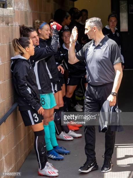 Seattle Reign FC head coach Vlatko Andonovski hi fives Seattle Reign FC goalkeeper Michelle Betos before the NWSL soccer match between the Sky Blue...
