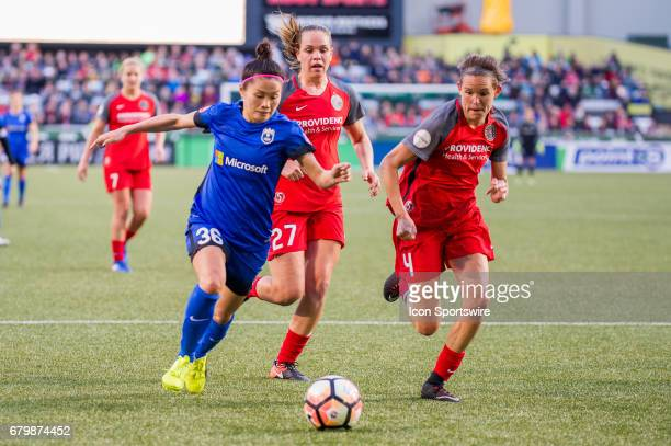 Seattle Reign midfielder Nahorri Kawasumi attemps a shot chased by Portland Thorns defenders Emily Menges and Meghan Cox during the 22 tie between...
