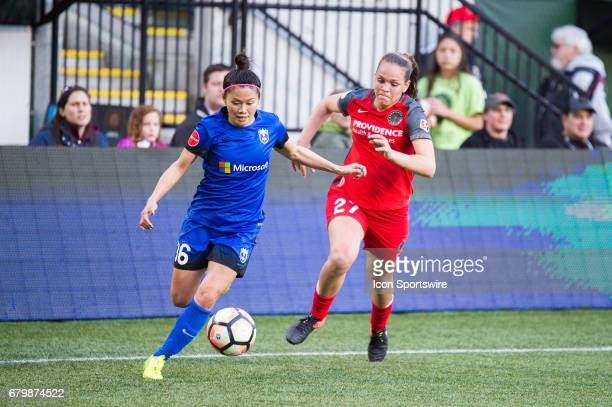 Seattle Reign midfielder Nahorri Kawasumi looks for a cross chased by Portland Thorns defender Meghan Cox during the 22 tie between Portland Thorns...