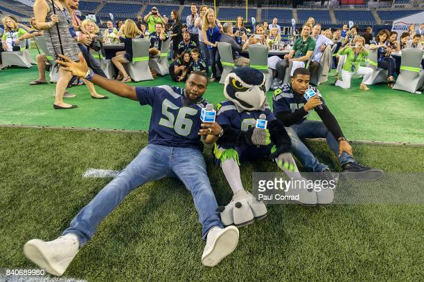 Seattle Seahawks Cliff Avil left mascot Blitz and Bobby Wagner have a fun moment with the guests during the American Express Dinner on the 50 at...