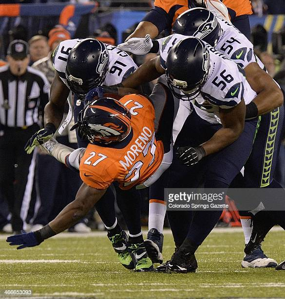 Seattle Seahawks defenders Chris Clemons left and Cliff Avril stop Denver Broncos running back Knowshon Moreno after a short gain in the first...