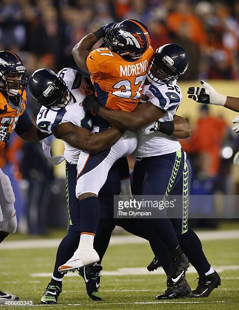 Seattle Seahawks defenders Chris Clemons left and Cliff Avril wrap up Denver Broncos running back Knowshon Moreno in Super Bowl XLVIII at MetLife...