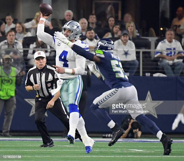 Seattle Seahawks defensive end Frank Clark pressures Dallas Cowboys quarterback Dak Prescott as he dumps it off to wide receiver Cole Beasley during...