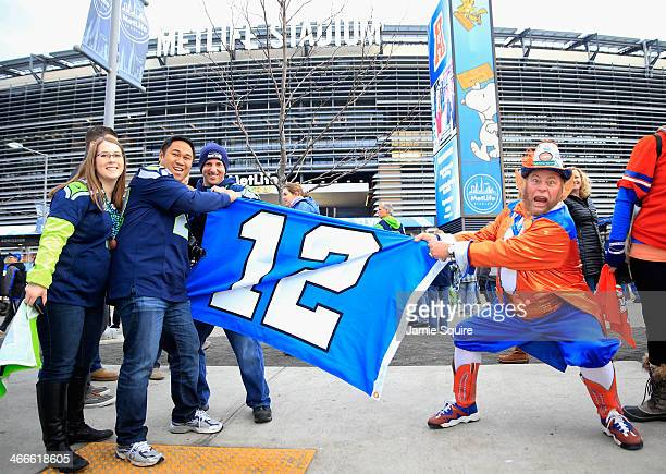 Seattle Seahawks fans hold an 12th Man Flag as a Denver fan attempts to pull it away prior to start of Super Bowl XLVIII against the Denver Broncos...