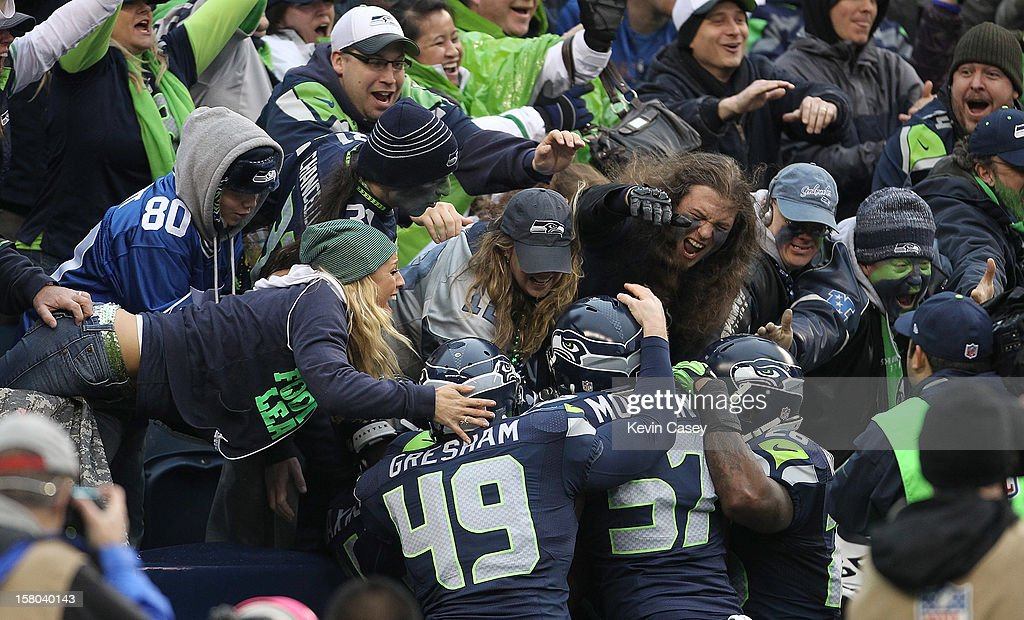 Seattle Seahawks fans swarm players after Malcolm Smith #53 scored a touchdown on a fumble recovery in the endzone against the Arizona Cardinals in the second quarter at CenturyLink Field on December 9, 2012 in Seattle, Washington.