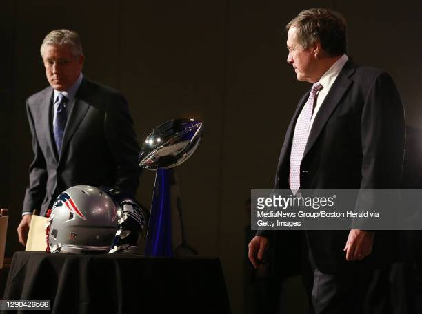 Seattle Seahawks head coach Pete Carroll, left, and New England Patriots head coach Bill Belichick stare at the Lombardi trophy at the Super Bowl...