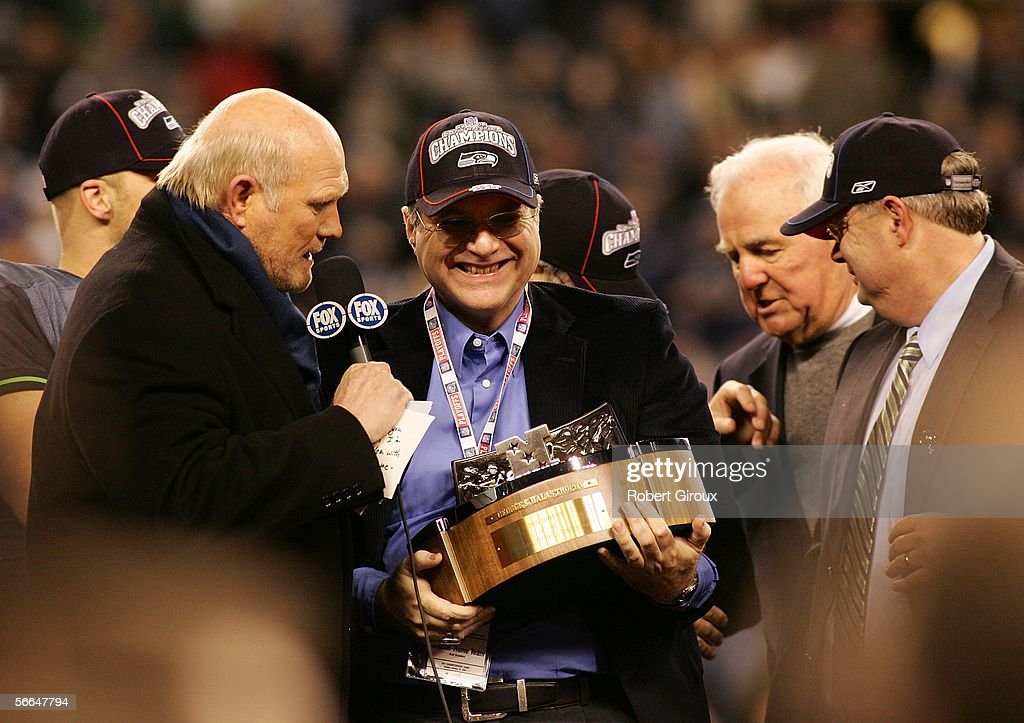 Seattle Seahawks owner Paul Allen (C) speaks with television commentator Terry Bradshaw (L) holds up the NFC Championship trophy following his team's victory over the Carolina Panthers at Qwest Stadium on January 22, 2006 in Seattle, Washington. Seattle will play Pittsburgh in Super Bowl XL.