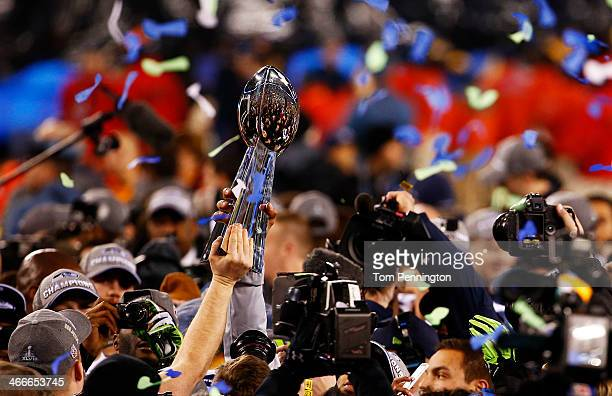 Seattle Seahawks players holds up Super Bowl Trophy after winning Super Bowl XLVIII at MetLife Stadium on February 2, 2014 in East Rutherford, New...