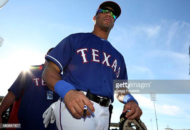 Seattle Seahawks QB Russell Wilson of the Texas Rangers signs autographs for fans following a spring training baseball game against the Cleveland...