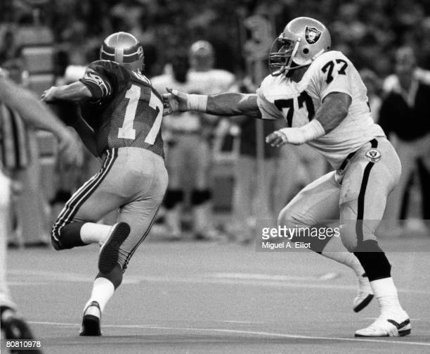 Seattle Seahawks quarterback Dave Krieg tries to avoid being tackled by Los Angeles Raiders end Lyle Alzado in a 13-7 win over the Los Angeles...