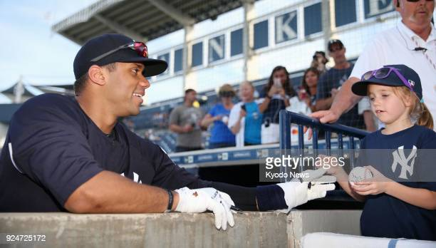 Seattle Seahawks quarterback Russell Wilson prepares to sign a ball for a fan at the New York Yankees' spring training site in Tampa Florida on Feb...