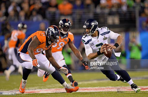 Seattle Seahawks quarterback Russell Wilson scrambles away from Denver Broncos defensive end Robert Ayers during the first quarter. The Denver...