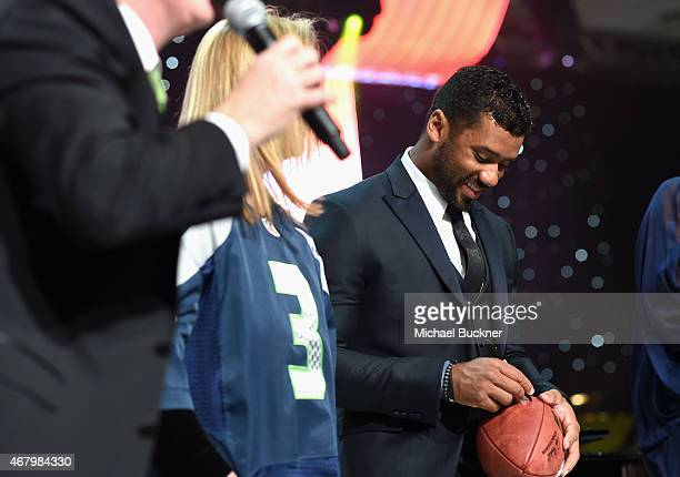 Seattle Seahawks quarterback Russell Wilson signs a football onstage during Muhammad Ali's Celebrity Fight Night XXI at the JW Marriott Phoenix...