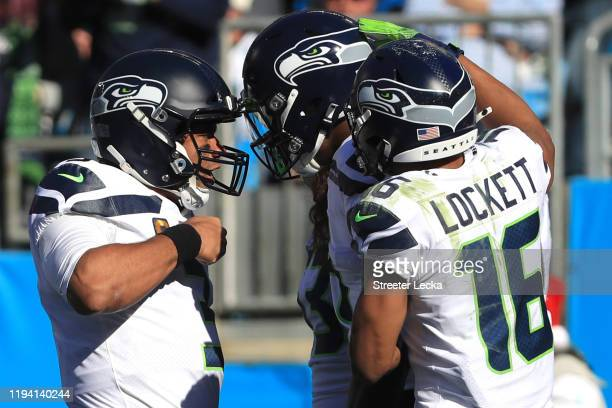 Seattle Seahawks quarterback Russell Wilson, wide receiver Tyler Lockett and wide receiver D.K. Metcalf celebrate the touchdown in the first quarter...
