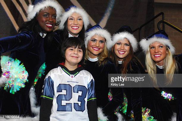 Seattle Seahawks Sea Gals cheerleaders pose with a young male fan wearing a No 23 Marcus Trufant jersey at Touchdown City during tailgate festivities...