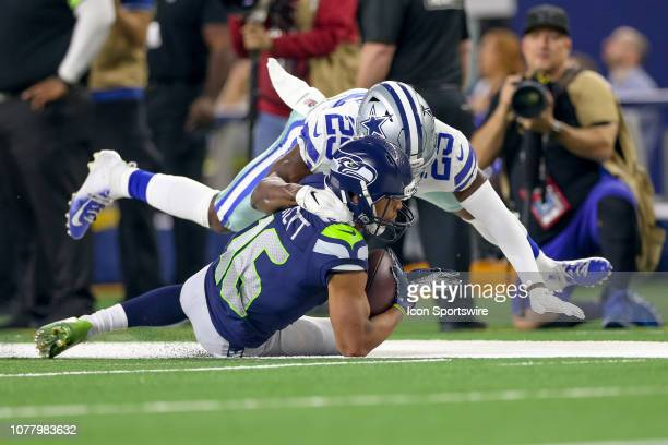 Seattle Seahawks wide receiver Tyler Lockett is tackled by Dallas Cowboys free safety Xavier Woods during the NFC wildcard playoff game between the...