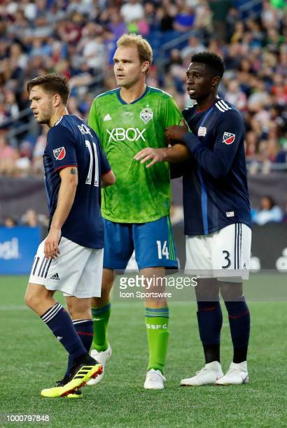 Seattle Sounders FC defender Chad Marshall draws New England Revolution midfielder Kelyn Rowe and New England Revolution defender Jalil Anibaba on a...