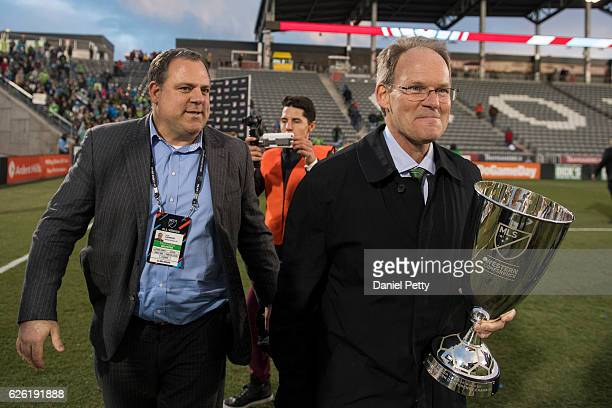 Seattle Sounders general manager Garth Lagerwey and Sounders coach Brian Schmetzer holding the MLS Western Conference trophy smile after the team...