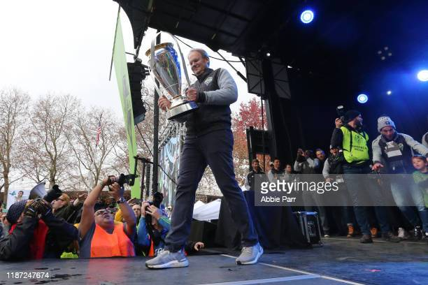 Seattle Sounders head coach Brian Schmetzer holds the MLS Cup trophy during the MLS Cup victory rally at the Seattle Center on November 12 2019 in...