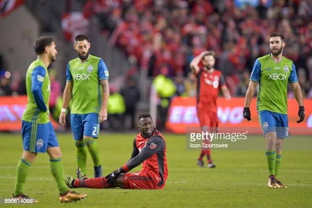 Seattle Sounders Midfielder Clint Dempsey and teammate Forward Will Bruin walk behind Toronto FC Forward Jozy Altidore sitting on the pitch during...
