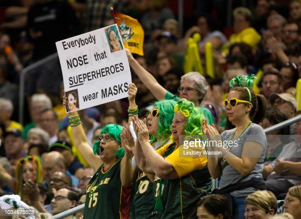 Seattle Storm fans cheer and hold a sign referencing Sue Bird's protective nose mask during the first half of Game 2 of the WNBA Finals at KeyArena...