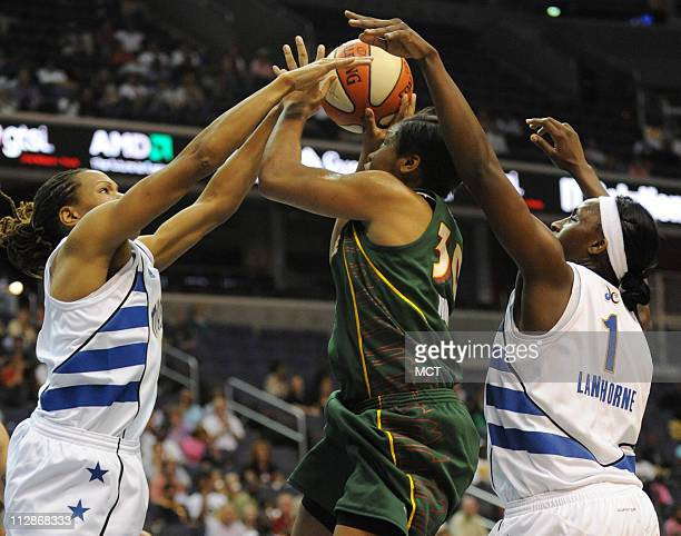Seattle Storm guard Tanisha Wright, center, tries to get a shot off while double-teamed by Washington Mystics Monique Currie, left, and Crystal...