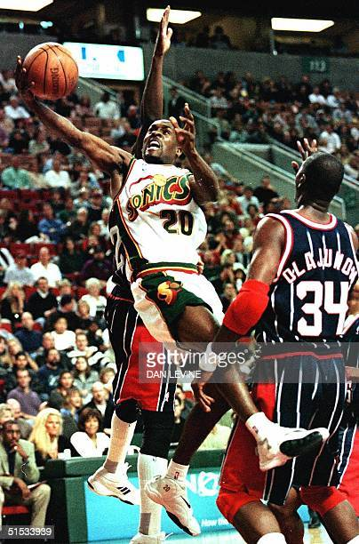 Seattle SuperSonic Gary Payton goes airborne against Houston Rocket Hakeem Olajuwon during their game 20 November 1999 in Seattle AFP PHOTO/Dan LEVINE
