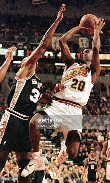 Seattle Supersonic Gary Payton goes up against San Antonio Spur Sean Elliott during first quarter action of their game in Seattle WA 26 February AFP...
