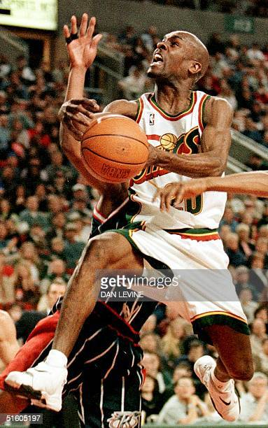 Seattle Supersonic Gary Payton goes up for a shot during second quarter action against Sam Mack of the Houston Rockets 04 April 1999 in Seattle...
