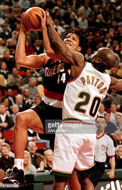 Seattle Supersonic Gary Payton tries to stop Brian Grant of the Portland Trailblazers during first half action of their game 08 April 1999 in Seattle...