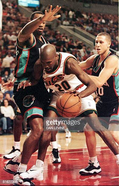Seattle Supersonics Gary Payton stumbles on his way to the basket against the defense of Vancouver Grizzlies Tony Massenburg and Mike Bibby during...