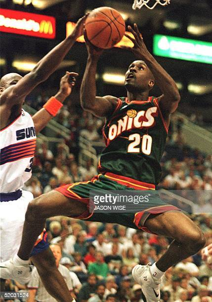 Seattle SuperSonics guard Gary Payton is blocked by Phoenix Suns forward Clifford Robinson during the first quarter 18 April 1999 in Phoenix Arizona