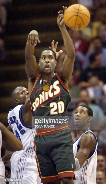 Seattle SuperSonics' guard Gary Payton makes a pass under pressure from Orlando Magic's guard Darrell Armstrong and forward Tracy McGrady during the...