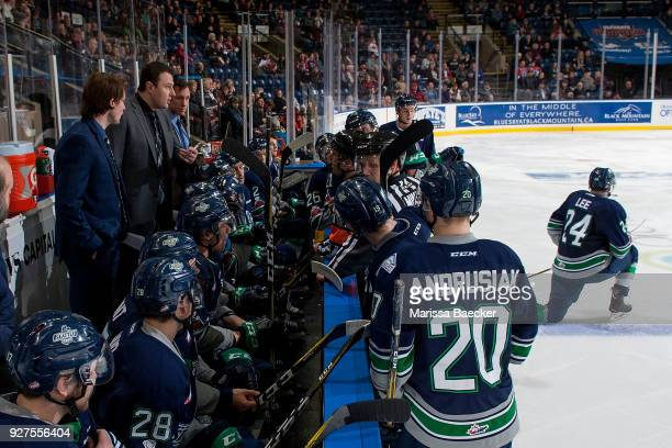 Seattle Thunderbirds' coaches Castan Sommer Matt O'Dette and Kyle Hagel stand on the bench during a time out and speak to referee Jeff Ingram against...