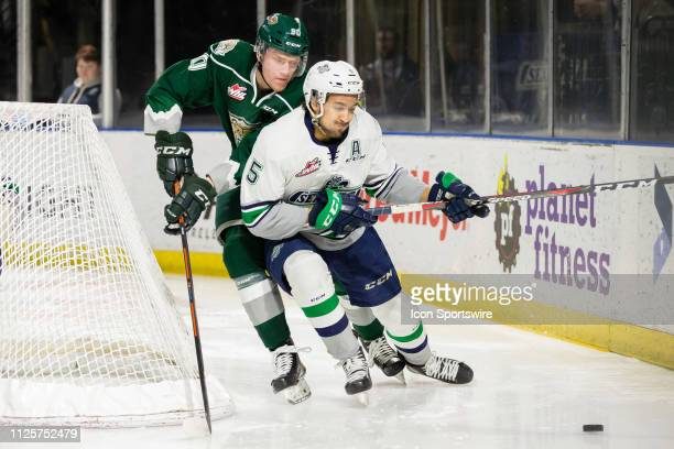Seattle Thunderbirds defenseman Jarret Tyszka shields Everett Silvertips forward Robbie Holmes from the puck behind the net in the first period of a...