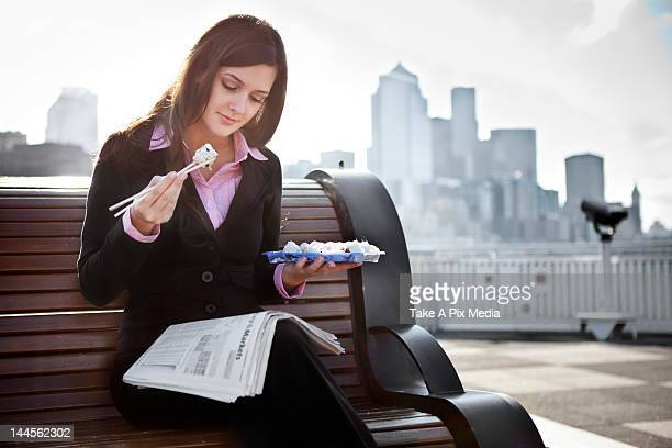 USA, Seattle, Young businesswoman eating sushi and reading newspaper