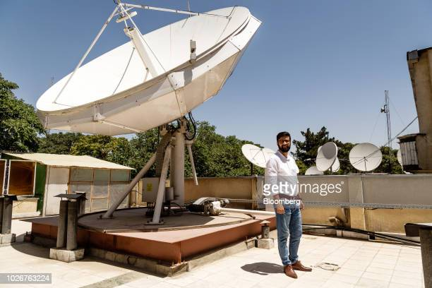 Seayer Ahadzada commercial director at Alef Technology stands for a photograph next to a parabolic antennae on the roof of the company's office in...