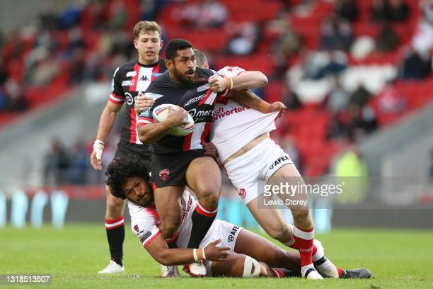 Seb Ikahihifo of Salford Red Devils is tackled by Agnatius Paasi and Kyle Amor of St Helens during the Betfred Super League match between St Helens...
