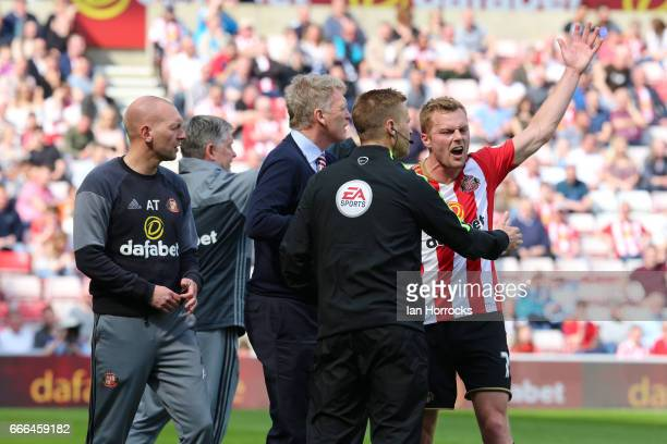 Seb Larsson of Sunderland argues with the fourth official during the Premier League match between Sunderland and Manchester United at Stadium of...