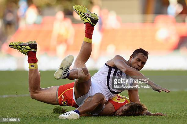 Seb Tape of the Suns is tackled by Shane Yarran of the Dockers during the round 18 AFL match between the Gold Coast Suns and the Fremantle Dockers at...