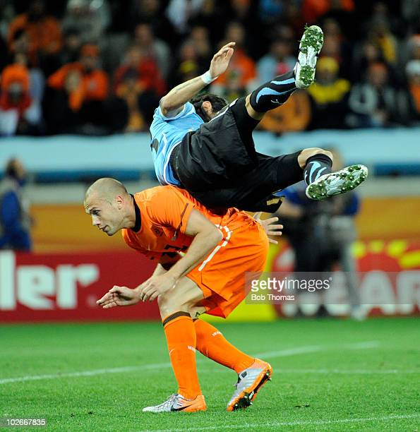 Sebastian Abreu of Uruguay falls over John Heitinga of the Netherlands during the 2010 FIFA World Cup South Africa Semi Final match between Uruguay...