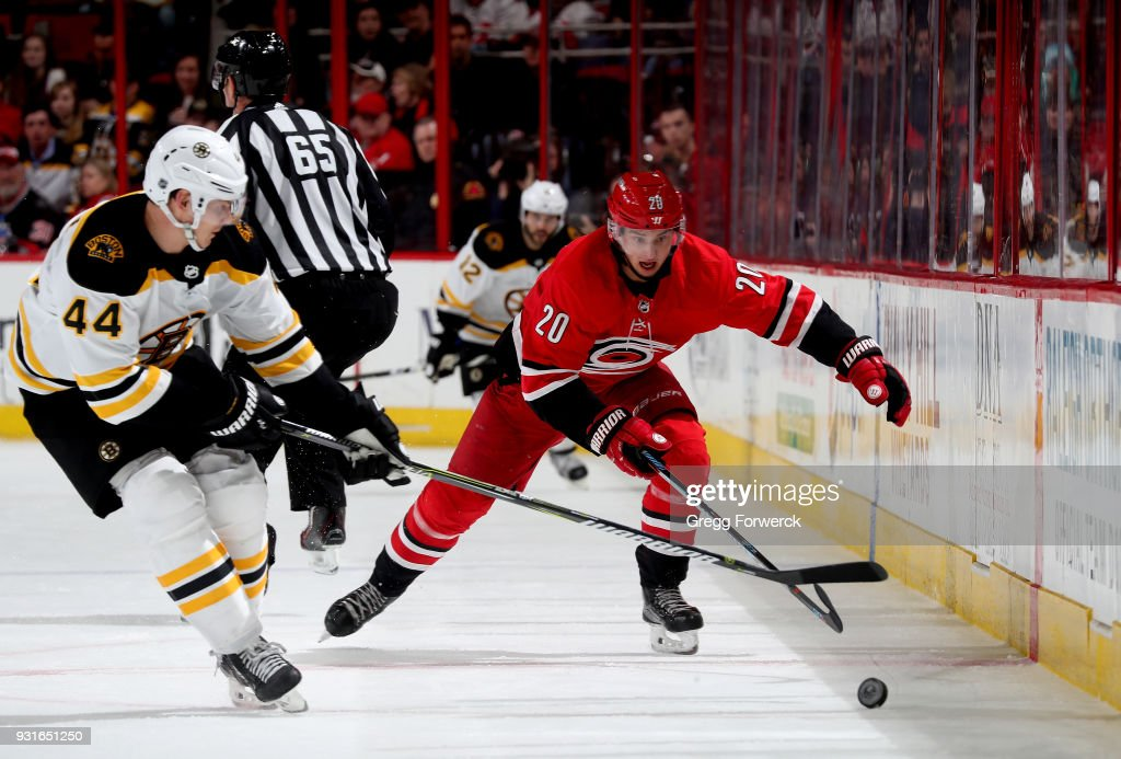 Sebastian Aho #20 of the Carolina Hurricanes and Nick Holden #44 of the Boston Bruins battle for the loose puck along the boards during an NHL game on March 13, 2018 at PNC Arena in Raleigh, North Carolina.