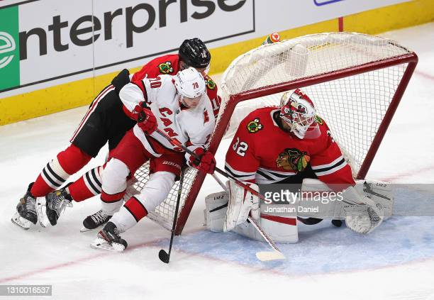 Sebastian Aho of the Carolina Hurricanes and Nikita Zadorov of the Chicago Blackhawks knock over the net as Kevin Lankinen makes a save under his leg...