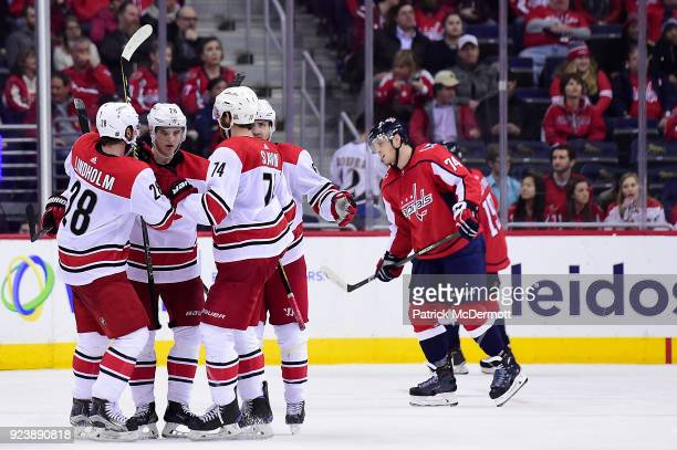 Sebastian Aho of the Carolina Hurricanes celebrates with his teammates Elias Lindholm and Jaccob Slavin after scoring an empty net goal against the...